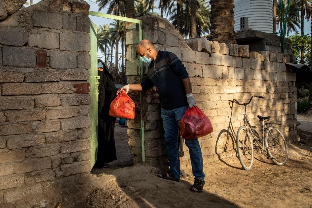 En man ger en fullpackad plastpåse till en kvinna över en tröskel.